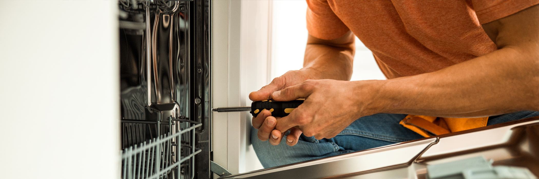 Close up of professional worker holding screwdriver to repair dishwasher.