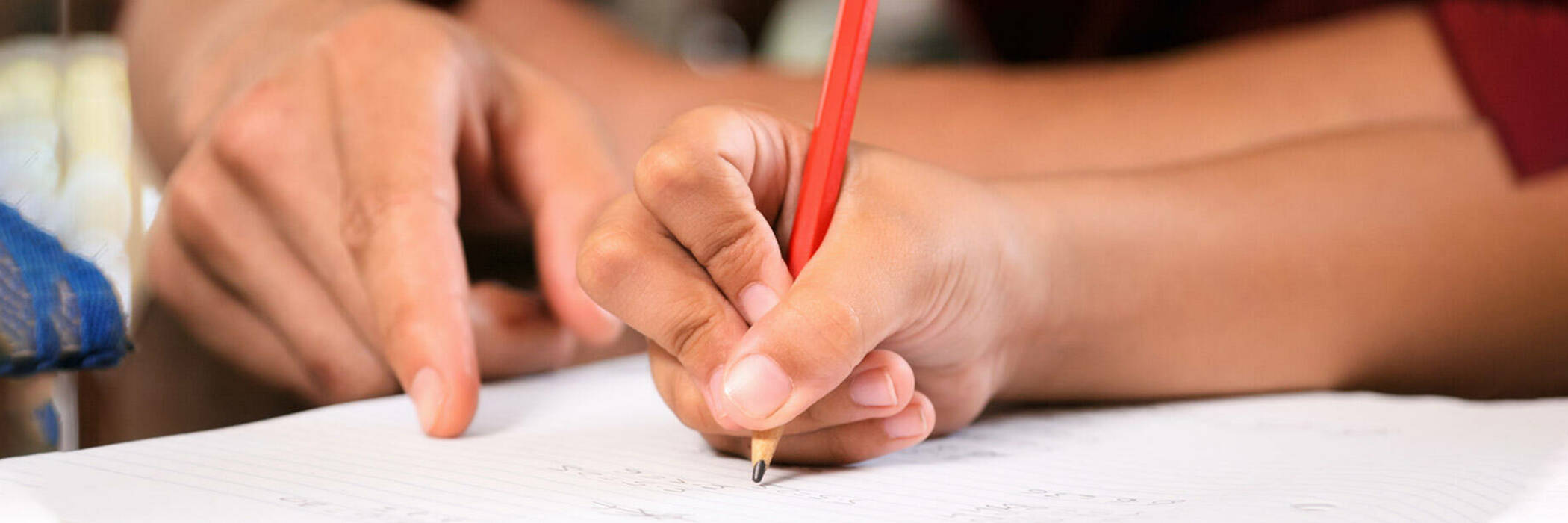 Student and tutor writing in pencil.