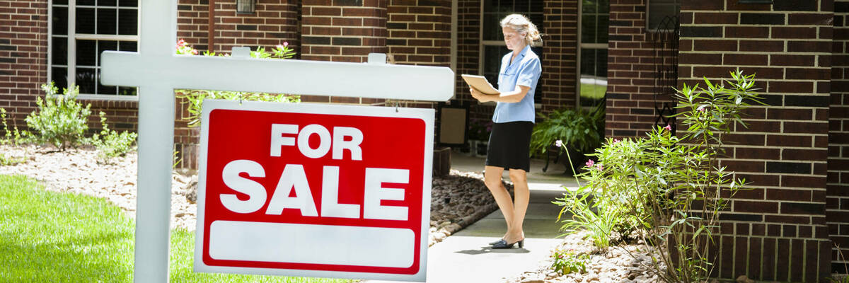Real estate agent behind a for sale sign.
