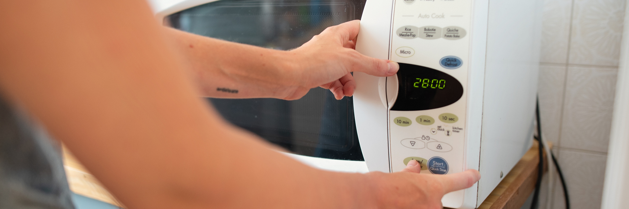 Close-up of a woman warming up food in a microwave while standing at a counter in her kitchen at home.