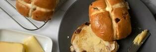 Buttered hot cross bun on a plate.
