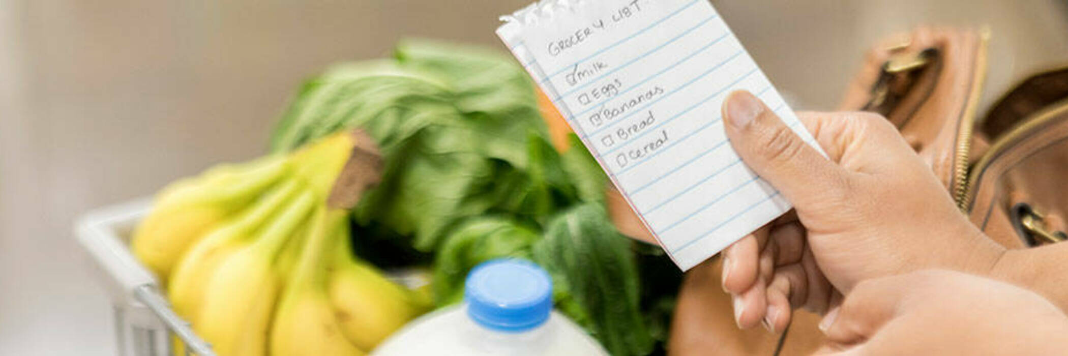 Supermarket shopper checks items off her grocery list.