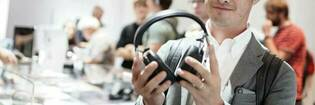 Man holding headphones at IFA Berlin.