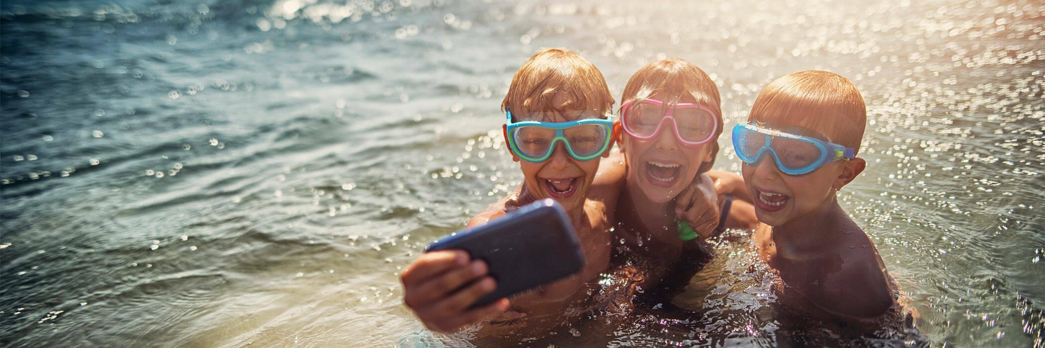 Kids taking selfies in the ocean.