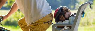 Child in rear-mounted bike seat.