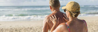 mature couple applying sunscreen at beach