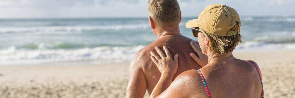 mature couple applying sunscreen at beach