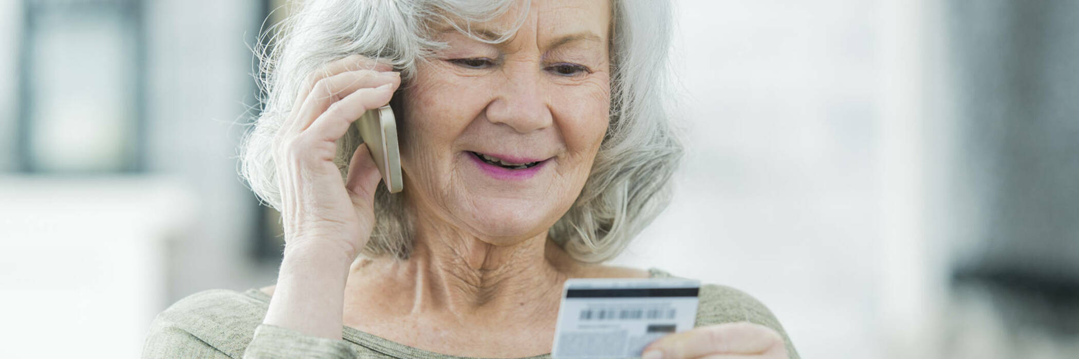 Senior woman making payment over the phone