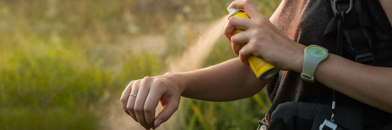 Close-up of young tourist applying mosquito spray on arms.