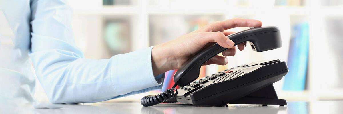 Person hanging up landline phone