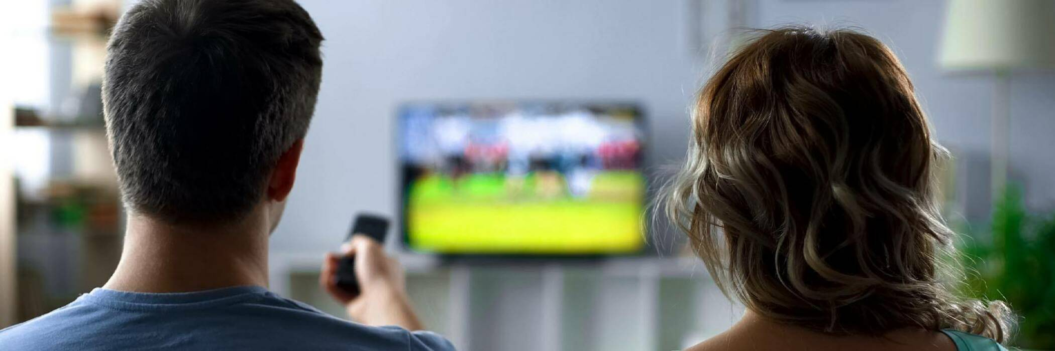 Couple watching sport on TV.