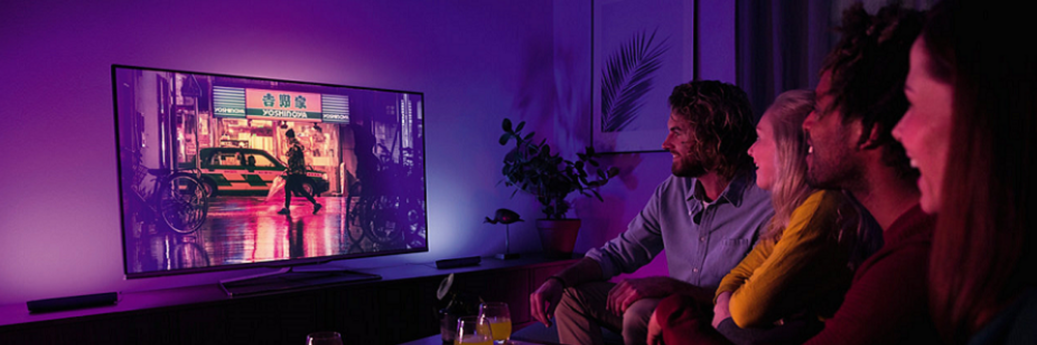 Friends watching TV lit by Philips Hue Play light bars.