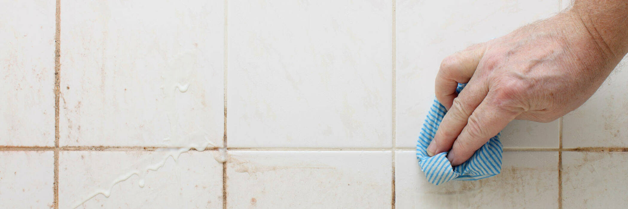 wiping dirty bathroom tiles