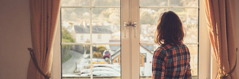 Young woman looking at windows during flat viewing