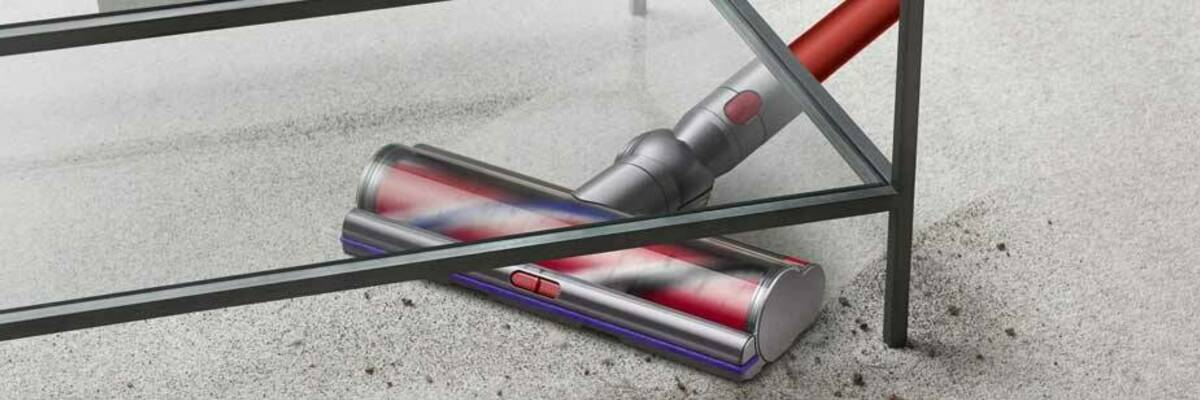 Dyson V11 Outsize stick vacuum cleaning under a table.