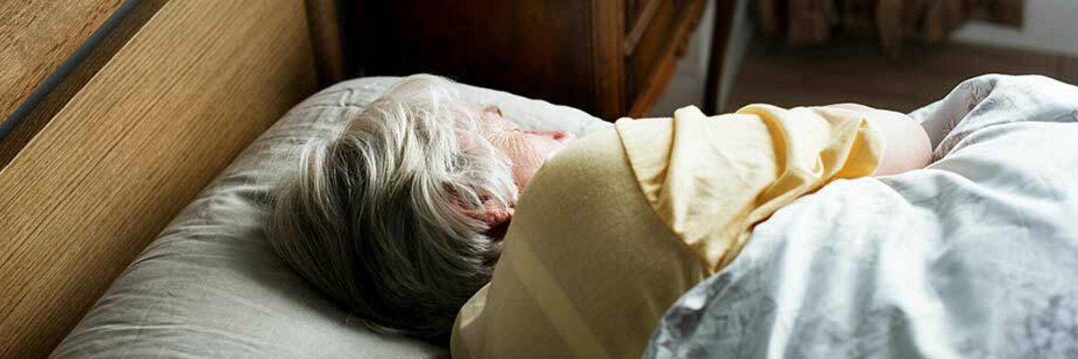 Elderly woman in bed in rest home.