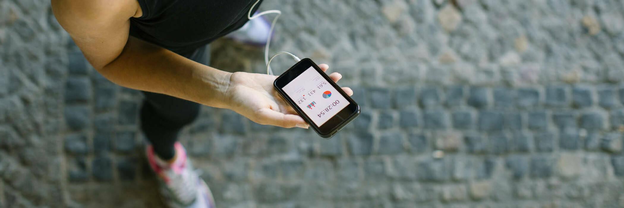 Woman using fitness app on phone.
