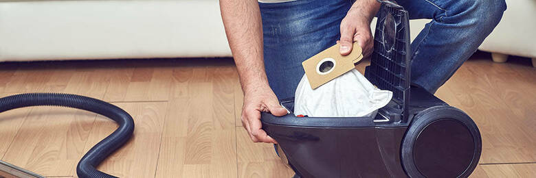 Man inserting a third-party bag vacuum bag into vacuum cleaner.