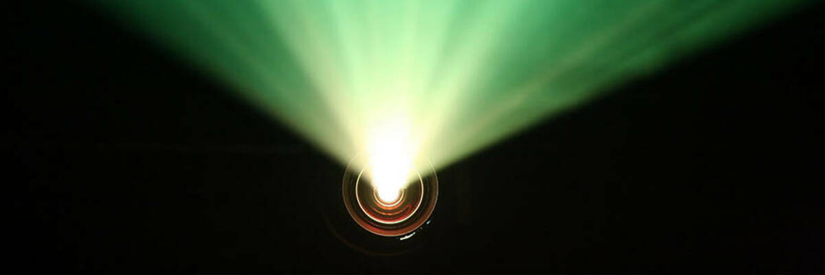 Beams of light from a projector in a dark room.