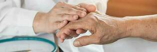 Doctor holding elderly patient's hand.