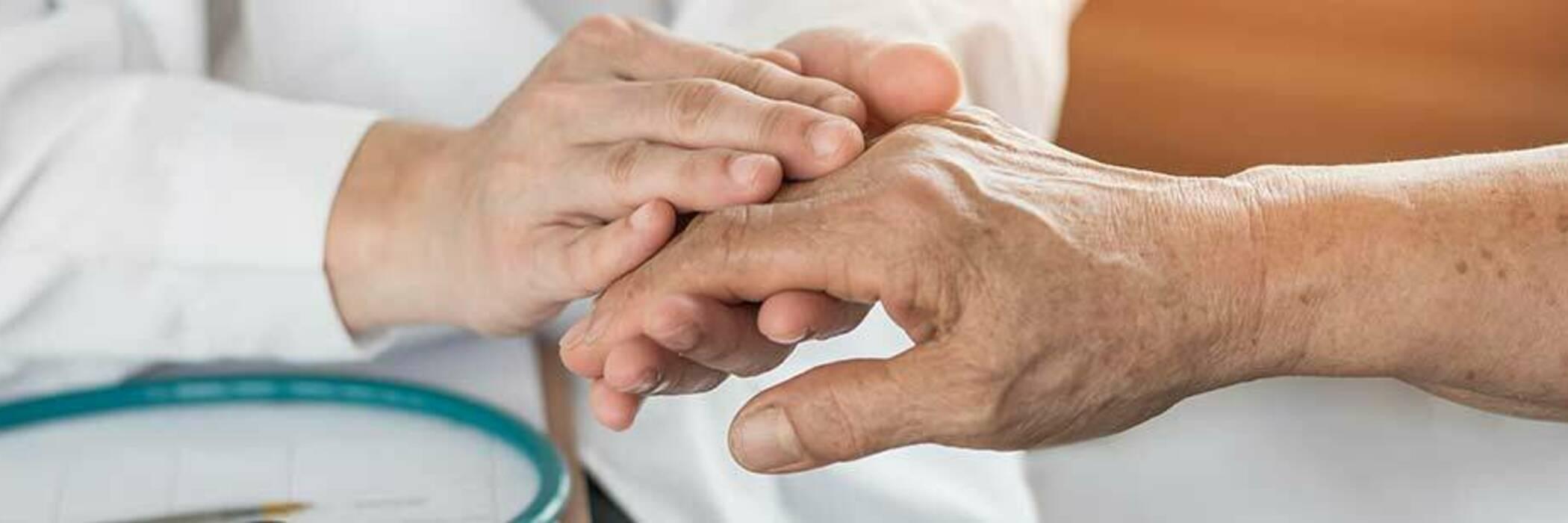 Doctor holding elderly patient's hand.