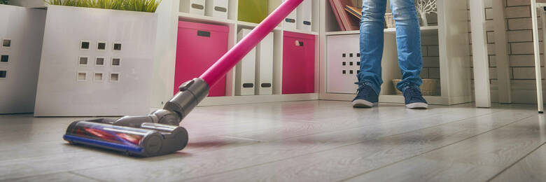 Person using cordless stick vacuum cleaner in kitchen.