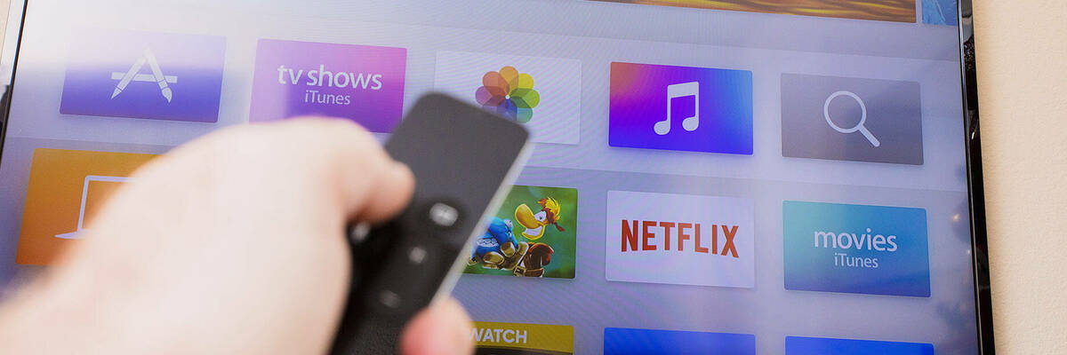 Selecting a streaming service on TV with remote.