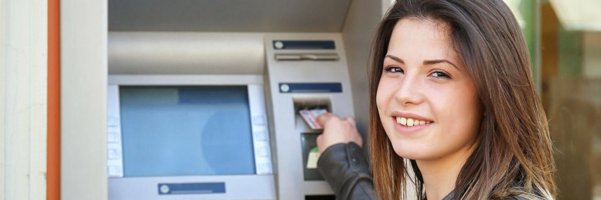 Woman inserting card into cash machine