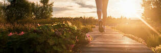 Close up of woman running in park at sunset.