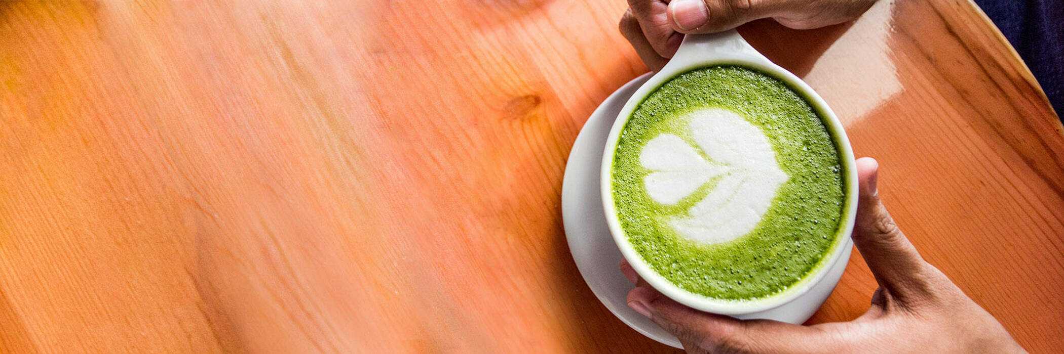 Man holding matcha latte at cafe