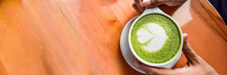 Man holding matcha latte at cafe