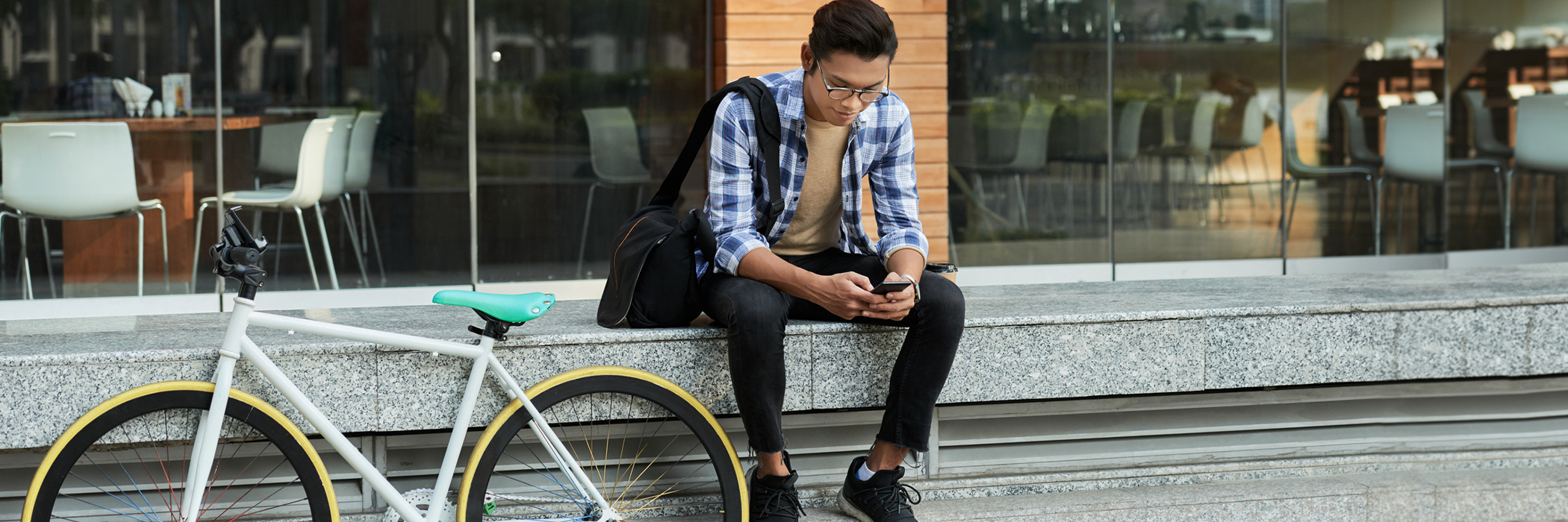 Portrait of cyclist sitting in front of modern coffee house and browsing Internet on smartphone.