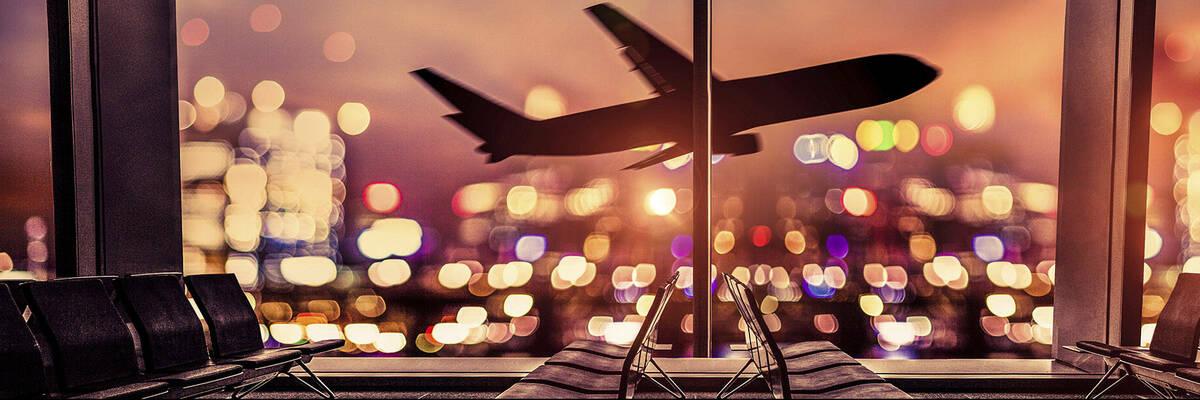 view through window of plane taking off at night