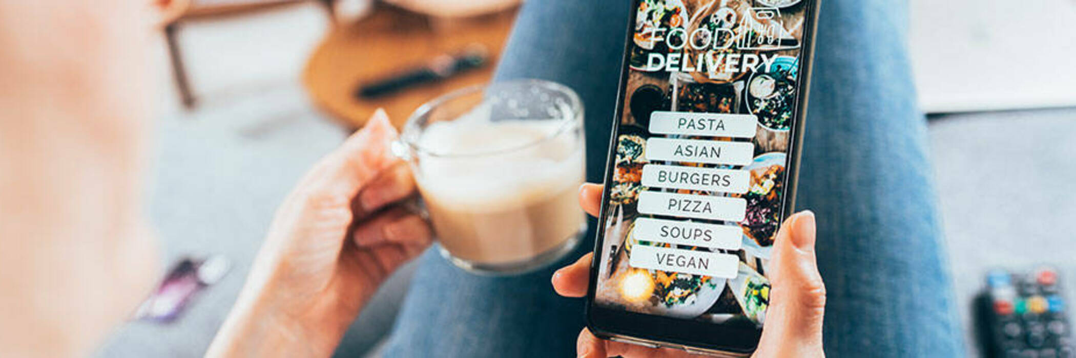 Woman using a food delivery app from a couch.