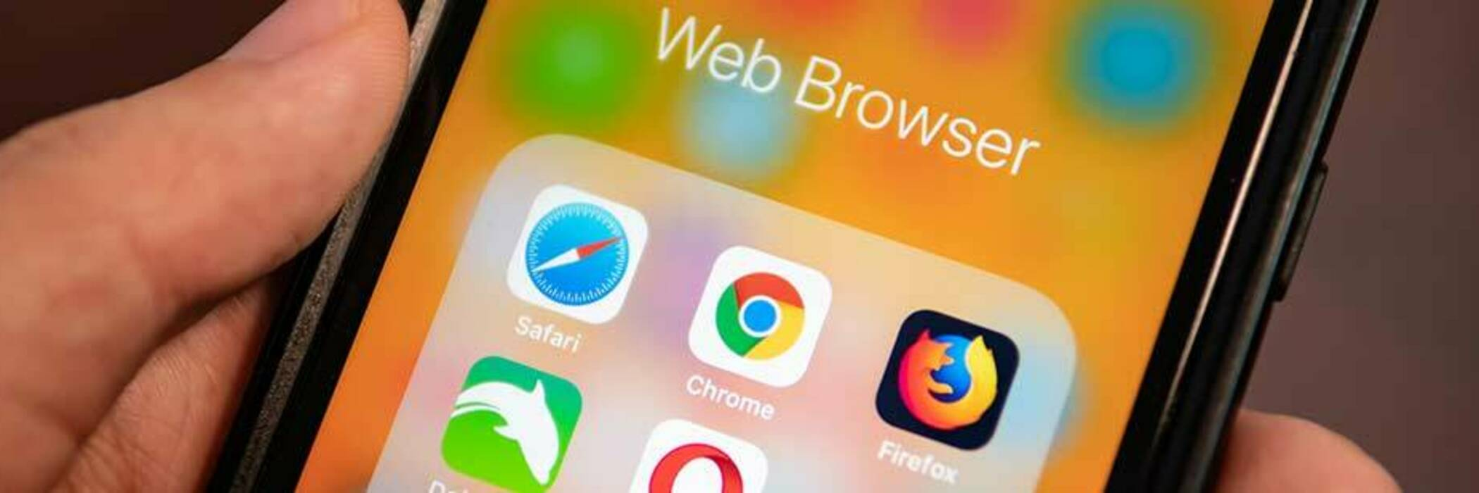 Hand holding a smartphone displaying icons for Google Chrome and other browsers.