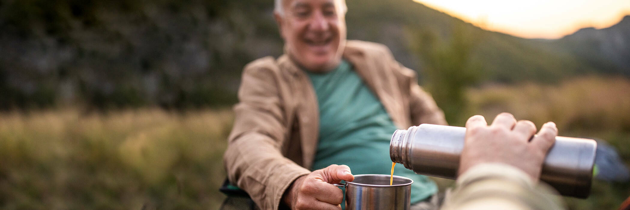 Man pouring coffee from thermos flask to his father while they're camping.