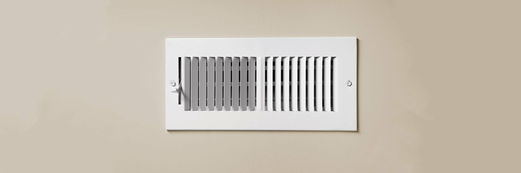 A cooling vent register on the wall of a home, with open lever.