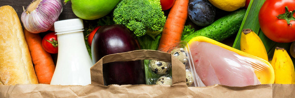 Meat, fruit, vegetables and bread in a paper bag.
