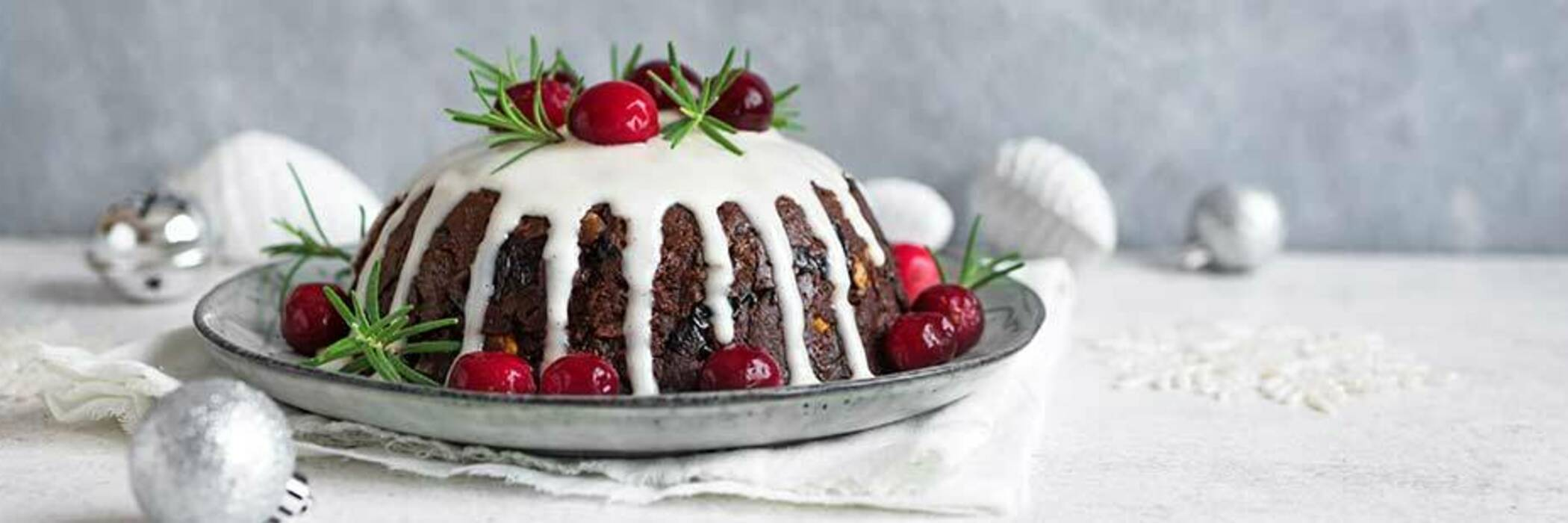 Christmas pudding topped with cherries and cream.