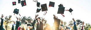 Graduates throwing graduation caps in the air