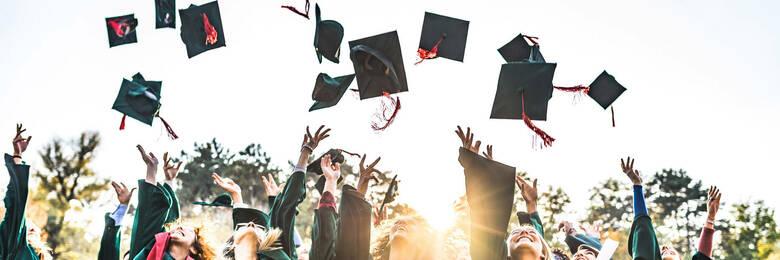Graduates throwing graduation caps in the air