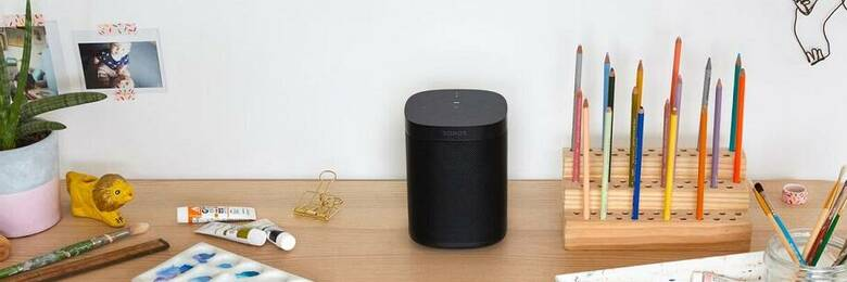 Black Sonos speaker on a desk surrounded by art supplies.