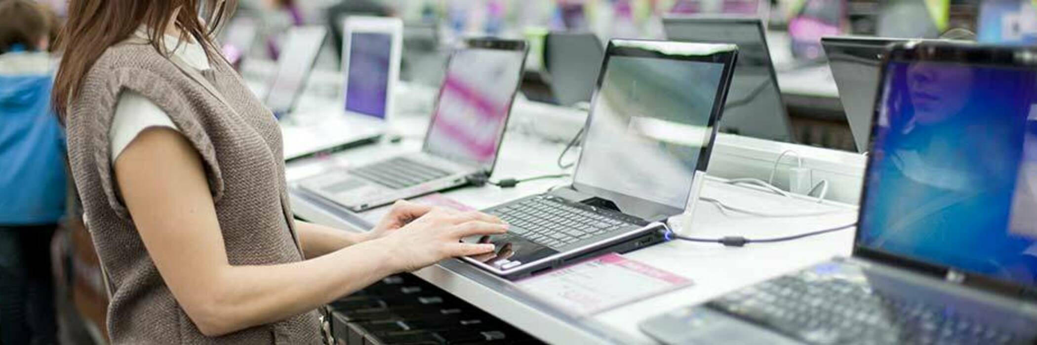 Woman typing on laptop in store.