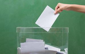 Placing a voting paper into a ballot box.