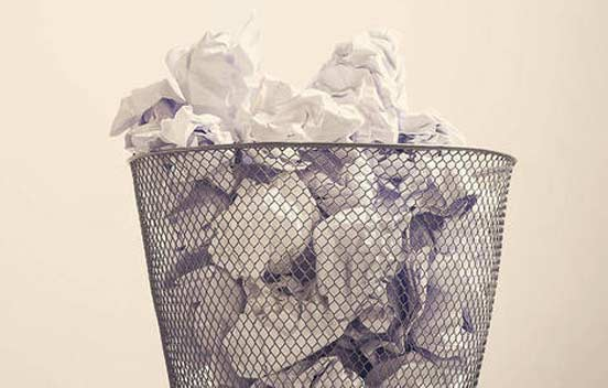Junk insurance policies in rubbish bin.