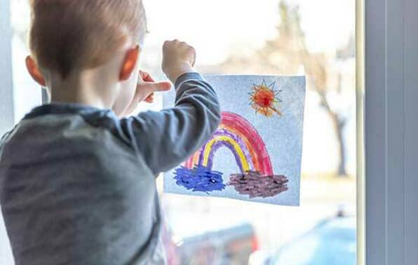 Young boy sticking drawing to window.