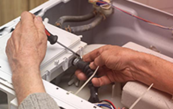 Service man with a screwdriver repairing a washing machine, indoor closeup.