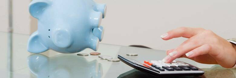 Table with calculator and piggy bank
