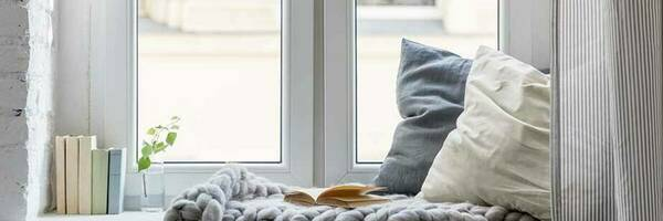 Cosy room with a window, curtains and blanket.