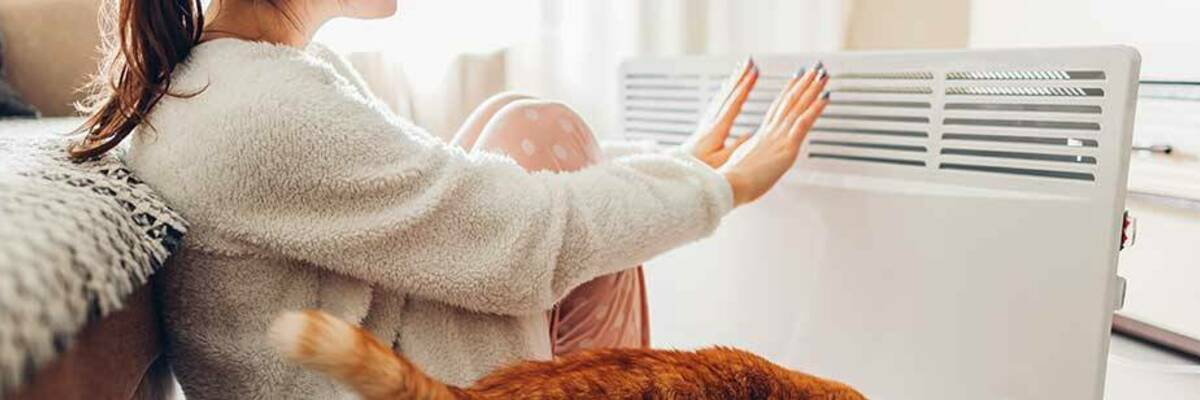 Woman warming her hands next to an electric heater.